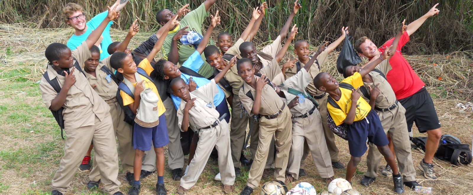 Des volontaires et enfants prennent la pose avant leur entraînement de football.